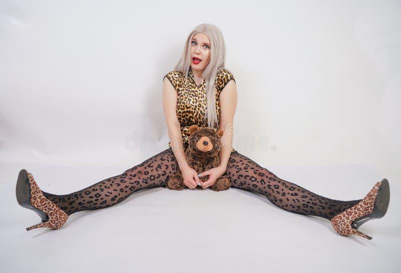 Belle blonde potelée de platine avec les lèvres rouges utilisant la robe courte d'impression de léopard et le collant noir sur photo stock