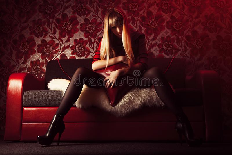Belle blonde sexuelle dans une robe rouge, endroit intime, sur un divan rouge, avec un fond rouge photos stock