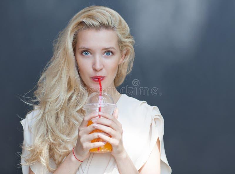 Belle blonde sexy avec des yeux bleus buvant la boisson par une paille un jour chaud d'été près du mur photo libre de droits