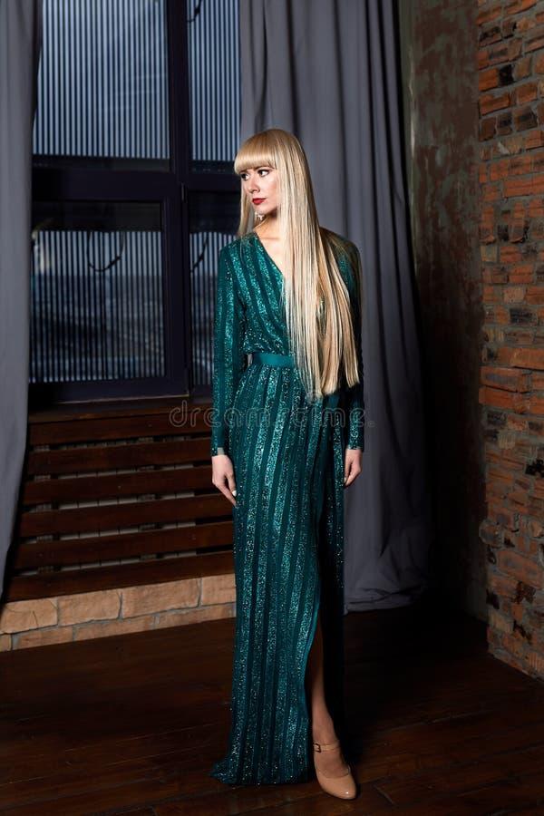 Belle blonde sexy de femme dans la robe de scintillement verte élégante Mannequin avec de longues jambes posant dans l'intérieur  image libre de droits
