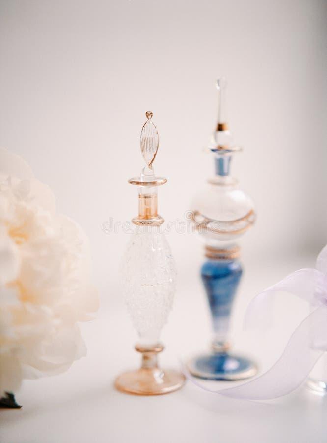 Belle bottiglie d'annata di profumo sulla tavola bianca fotografie stock libere da diritti