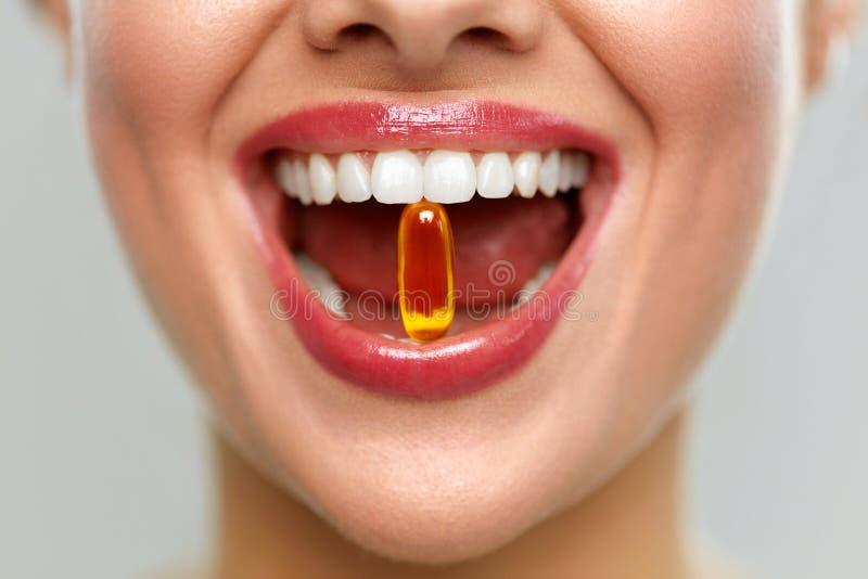 Belle bouche de femme avec la pilule dans des dents Fille prenant des vitamines images stock