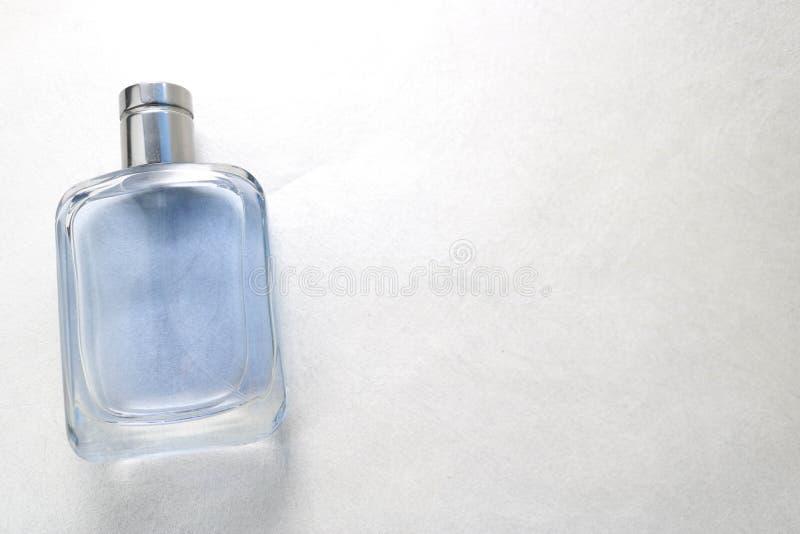 Belle bouteille fascinante à la mode brillante transparente en verre rectangulaire bleue de cologne, de parfum avec l'encadrement photos libres de droits