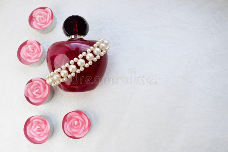 Belle bouteille transparente en verre pourpre de parfum femelle décorée des perles ternes blanches et des bougies roses de paraff images libres de droits