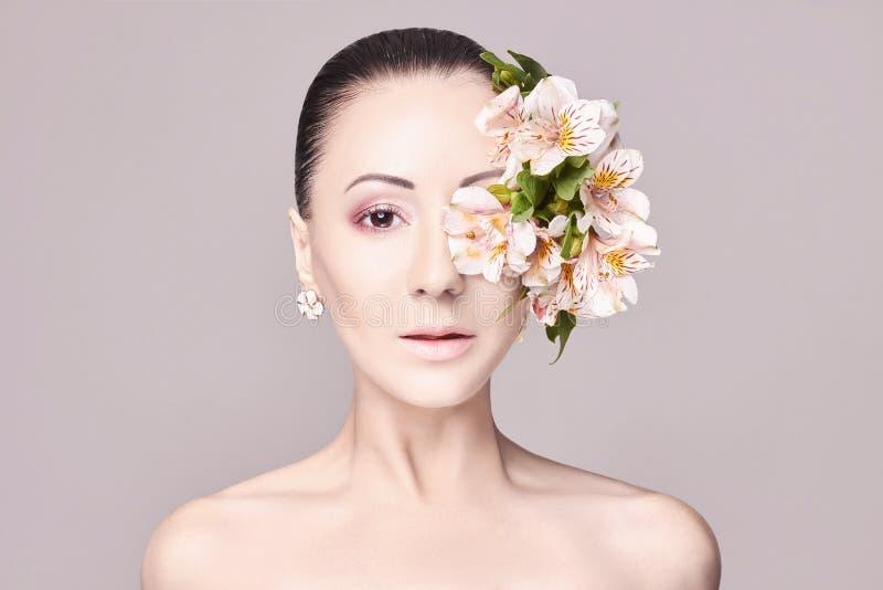 Belle brune attrayante nue avec des fleurs sur sa tête Façonnez le beau maquillage, peau propre, soin facial Verticale des jeunes photographie stock