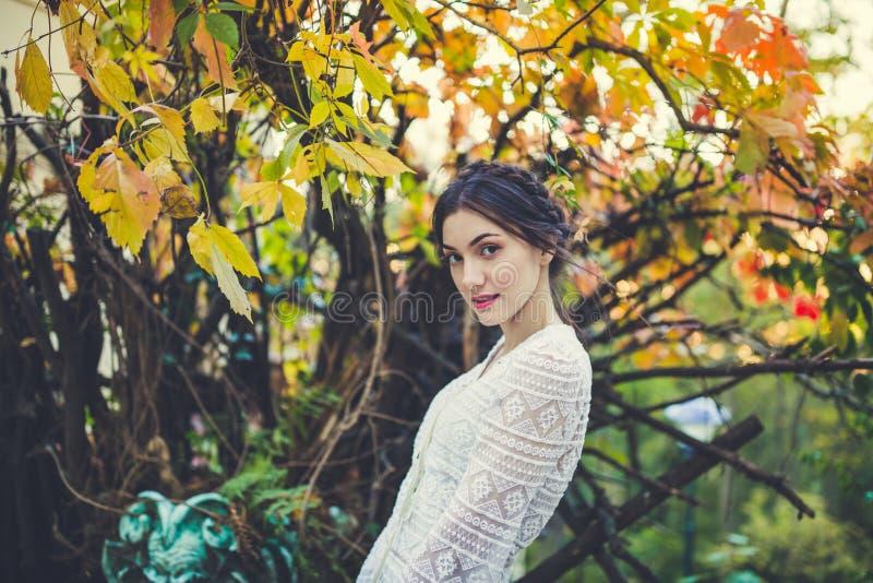 Belle brune avec des tresses autour de tête dans chemisier de douille de dentelle blanche de cru un long en parc d'automne photographie stock