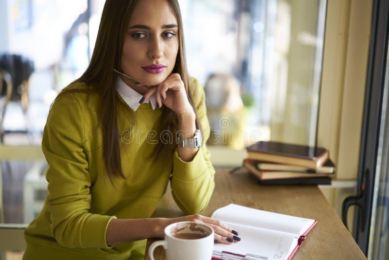 Belle brune dans un chemisier jaune dans le journal intime pour créer des caractères des étrangers en dehors de la fenêtre photos libres de droits