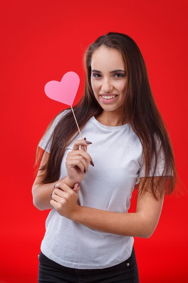 Belle brune de fille tenant un coeur de papier rose sur un bâton et souriant heureusement image stock