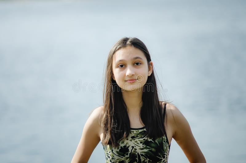 Belle brune de l'adolescence de fille avec de longs cheveux sur le fond de ciel bleu photos libres de droits