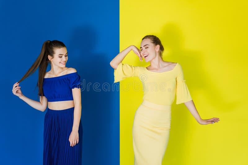 Belle brune et filles blondes dans la pose bleue et jaune d'équipements photos libres de droits