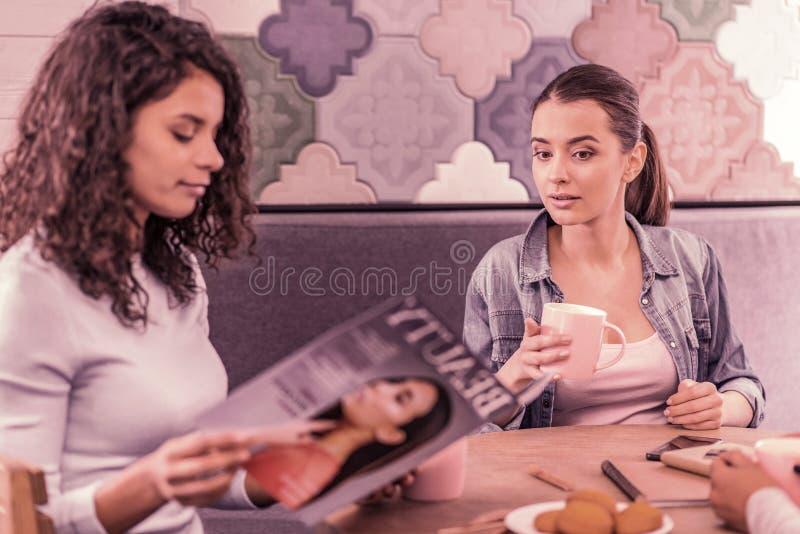 Belle brune interrogeant son ami au sujet de la revue de mode dans des ses mains images stock