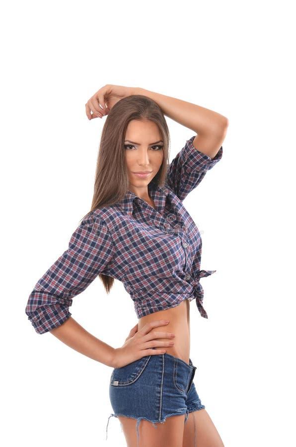 Belle brune posant avec une main sur la taille et l'autre au-dessus de sa tête images stock