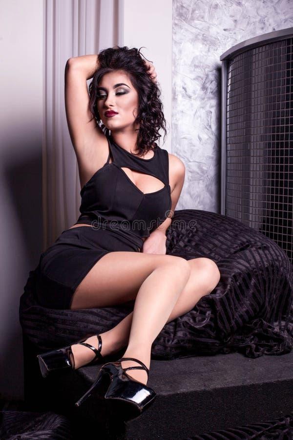 Belle brune posant pour l'appareil-photo portant la robe franche noire Femme avec les cheveux foncés bouclés et les lèvres rouges image libre de droits