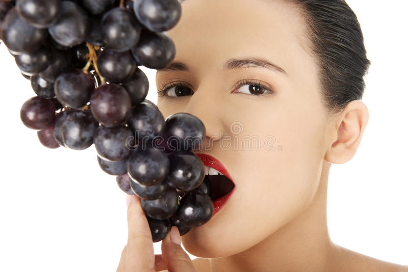 Belle brune sensuelle mangeant des raisins photo stock