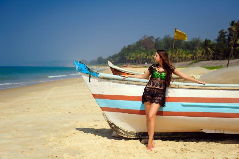 Belle brune sexy sur la plage sablonneuse tropicale près du bateau en bois sur le fond bleu de mer et du ciel clair le jour ensol photo stock