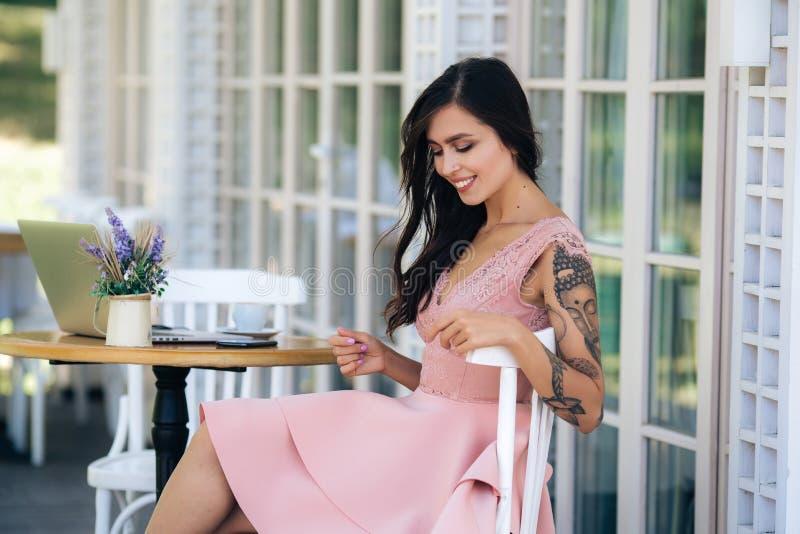 Belle brunette avec un beau sourire en robe rose est assise au café de rue photo stock