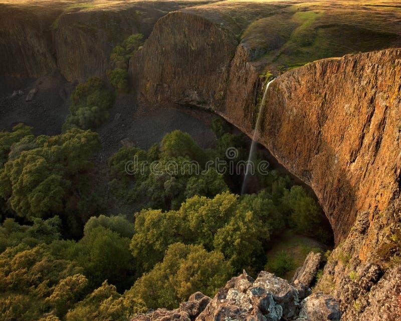 Belle cascade à écriture ligne par ligne au-dessus de falaise au coucher du soleil photographie stock