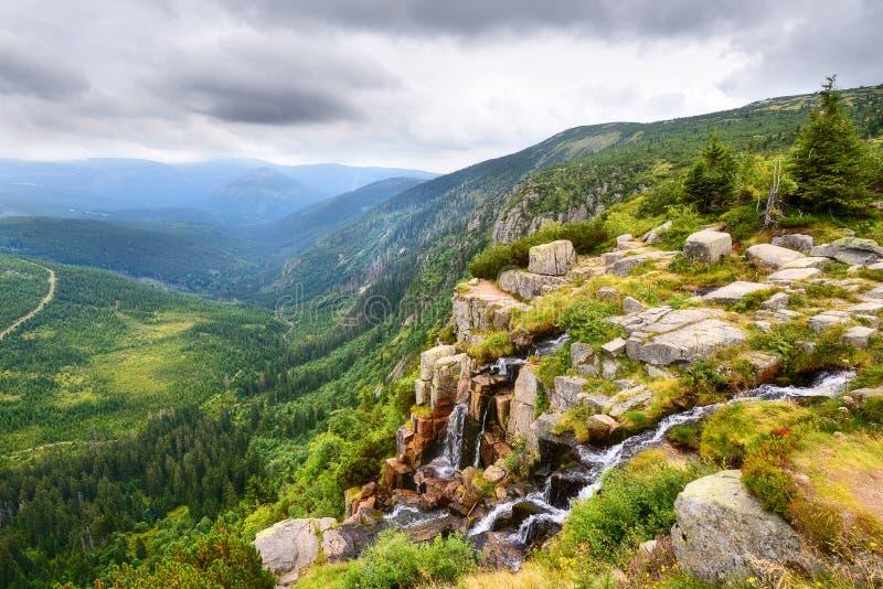 Belle cascade au-dessus d'une vallée vert-foncé dans les montagnes photo libre de droits