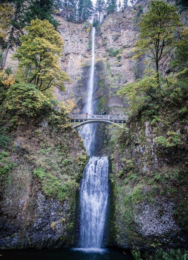 Belle cascade entourée par la verdure et un pont en quelques automnes de Multnomah, Etats-Unis photographie stock