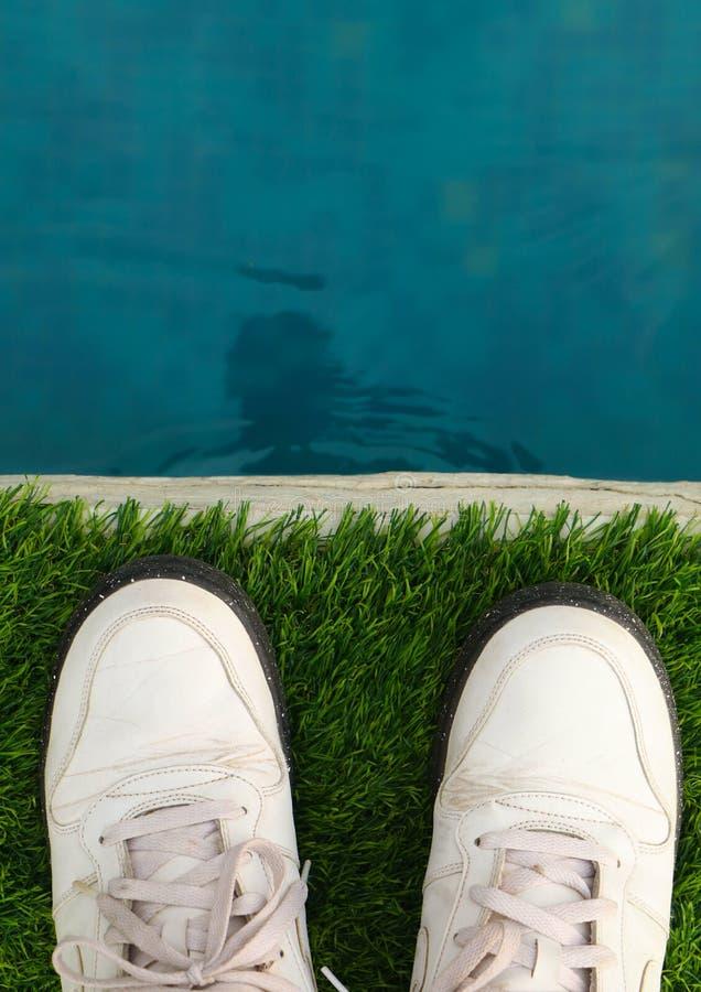 Belle combinaison de l'eau bleue et d'herbe verte de gazon artificiel avec les chaussures blanches wallpaper photos libres de droits