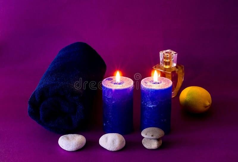 Belle composition de traitement de station thermale avec les bougies et la serviette bleues aromatiques sur le fond pourpre image stock