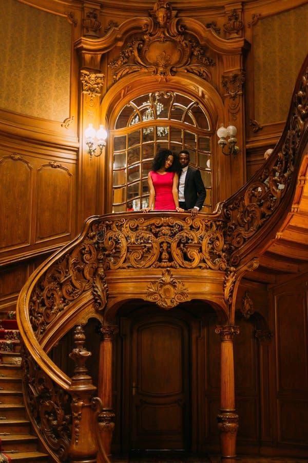 Belle coppie africane che posano sulle scale d'annata Fondo lussuoso dell'interno del teatro immagine stock