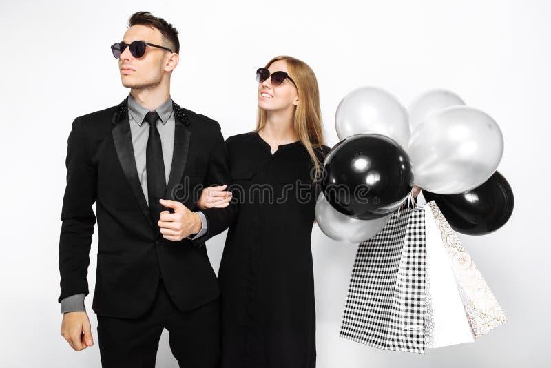 Belle coppie alla moda, ragazza in un vestito nero e un uomo fotografie stock