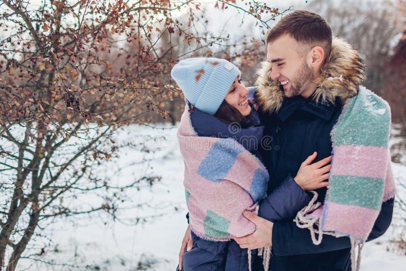 Belle coppie amorose che camminano e che abbracciano nel riscaldamento della gente della foresta di inverno coperto di coperta immagini stock libere da diritti