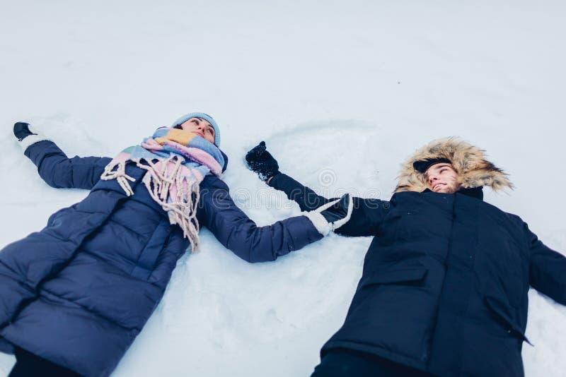 Belle coppie amorose che fanno gli angeli della neve nella foresta di inverno che si trova nella neve La gente divertendosi all'a fotografia stock libera da diritti