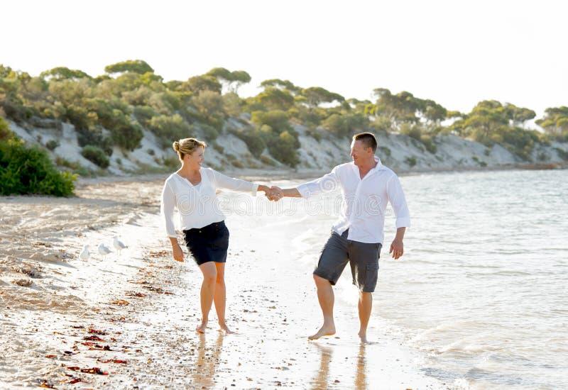 Belle coppie attraenti nell'amore che cammina sulla spiaggia nelle vacanze estive romantiche fotografia stock libera da diritti