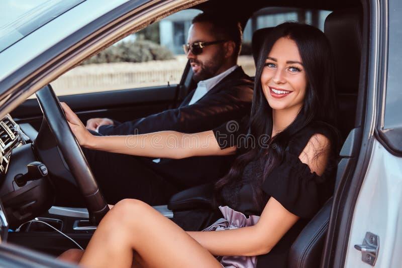 Belle coppie ben vestito che si siedono sui sedili anteriori nell'automobile di lusso immagini stock libere da diritti