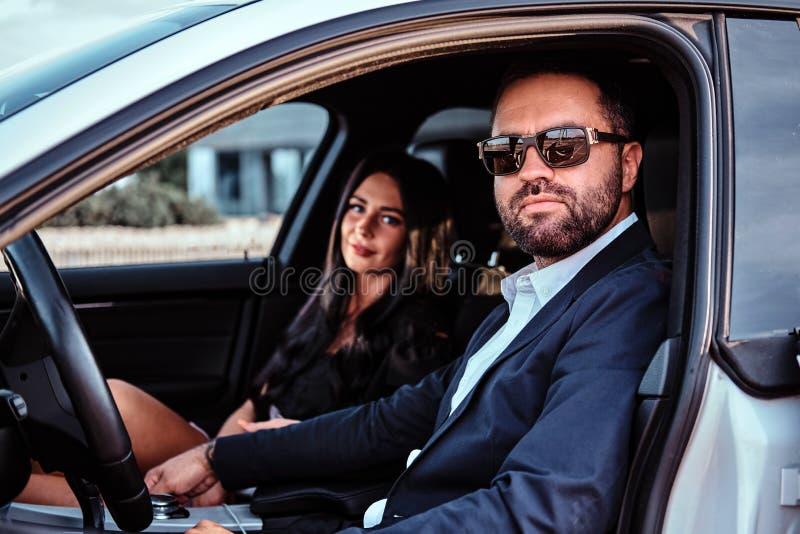 Belle coppie ben vestito che si siedono sui sedili anteriori nell'automobile di lusso fotografia stock libera da diritti