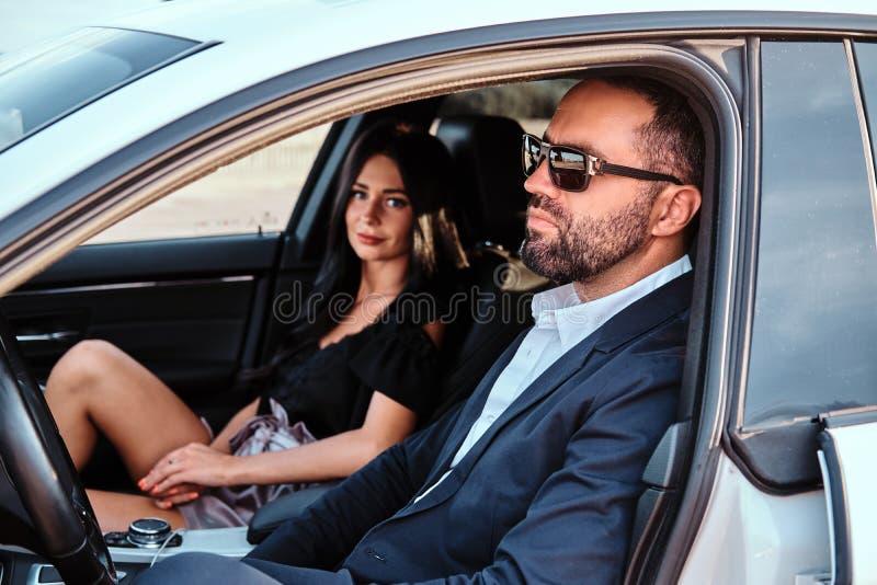 Belle coppie ben vestito che si siedono sui sedili anteriori nell'automobile di lusso immagini stock