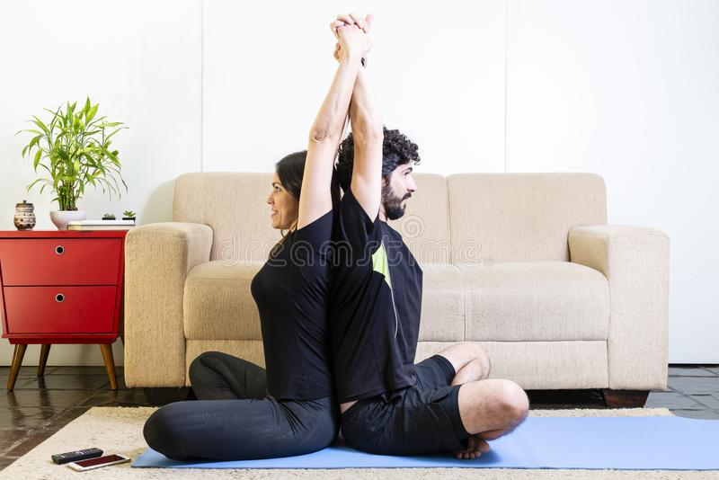 Belle coppie caucasiche etere in vestiti neri su yogam blu fotografia stock libera da diritti