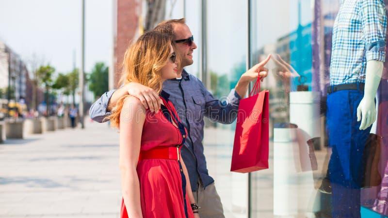 Belle coppie che camminano attraverso il centro commerciale che porta molti sacchetti della spesa. fotografia stock libera da diritti