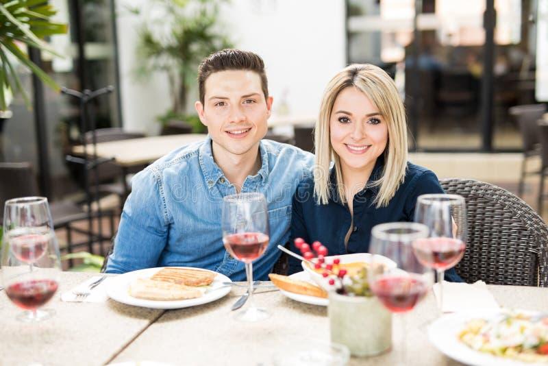 Belle coppie che mangiano fuori con gli amici fotografia stock libera da diritti