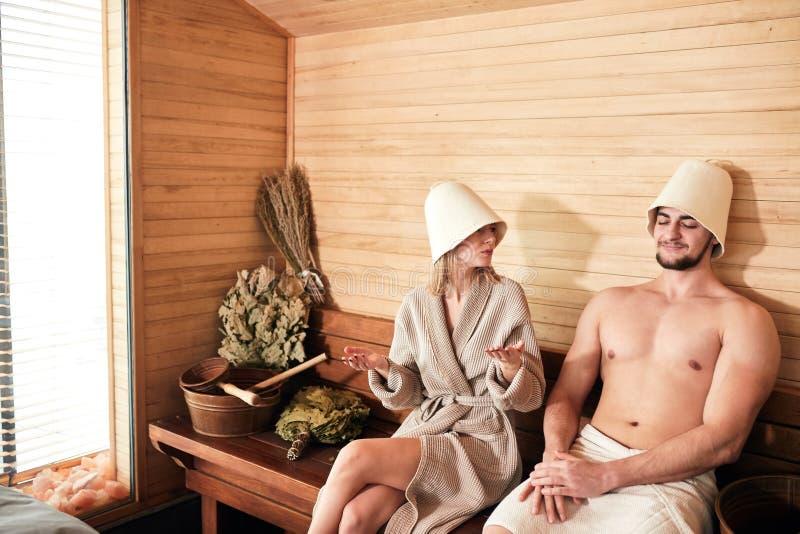 Belle coppie che si rilassano nella sauna e che si preoccupano per la salute e la pelle immagini stock