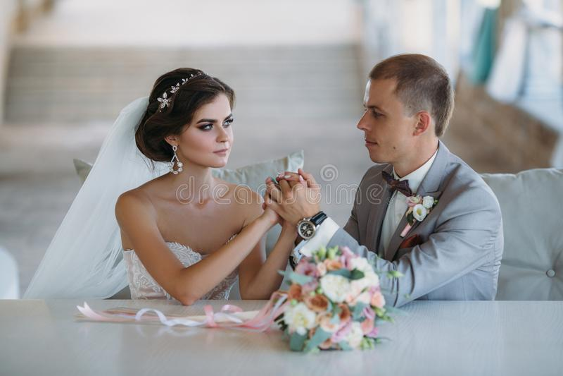 Belle coppie di nozze che abbracciano nel parco con gli alberi verdi su fondo Sposo in un vestito grigio di affari, camicia bianc fotografia stock libera da diritti