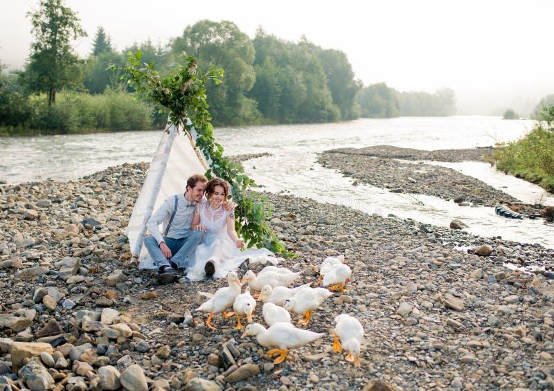 Belle coppie di nozze che stanno vicino alla montagna con la vista perfetta fotografia stock
