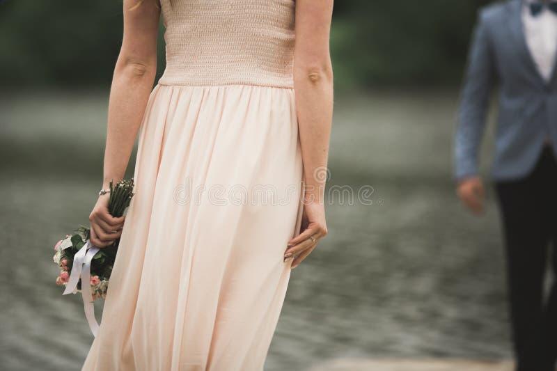 Belle coppie di nozze, sposa, sposo che bacia e che posa sul ponte vicino al lago fotografie stock
