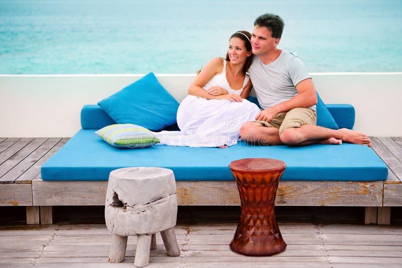 Belle coppie felici che si distendono in caffè della spiaggia immagine stock libera da diritti