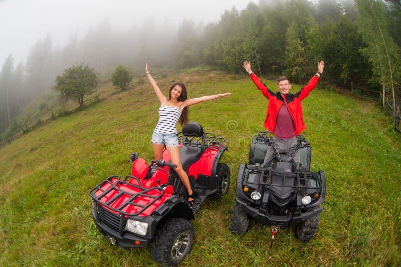 Belle coppie felici che si siedono sui veicoli a quattro ruote ATV fotografia stock libera da diritti