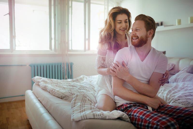 Belle coppie felici che svegliano sorridere nella camera da letto immagini stock libere da diritti