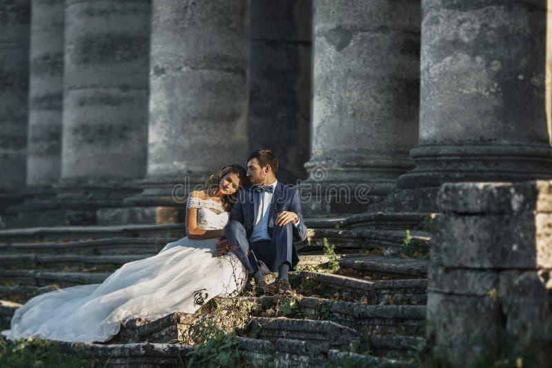 Belle coppie romantiche del biglietto di S. Valentino che si siedono sulle vecchie scale di pietra immagini stock