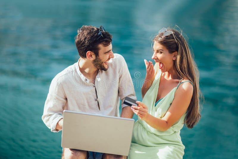 Belle coppie romantiche facendo uso del computer portatile e carta di credito dal porto fotografie stock libere da diritti