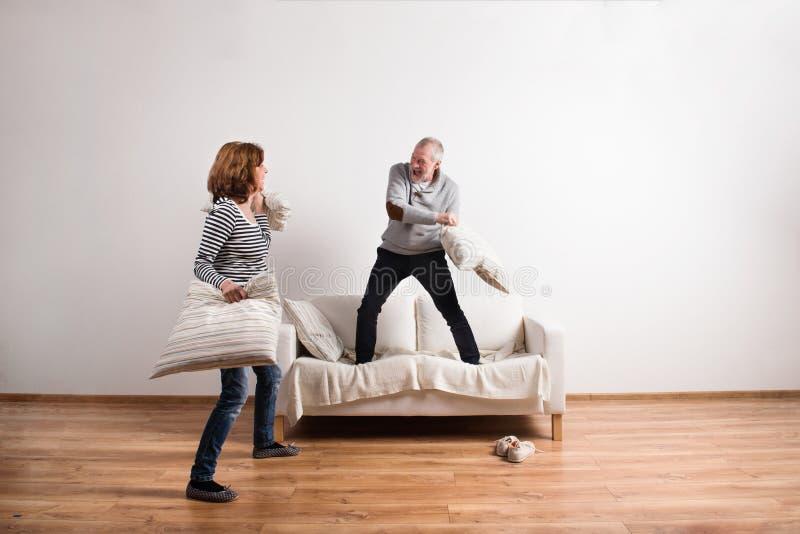 Belle coppie senior che hanno una lotta di cuscino Colpo dello studio fotografia stock