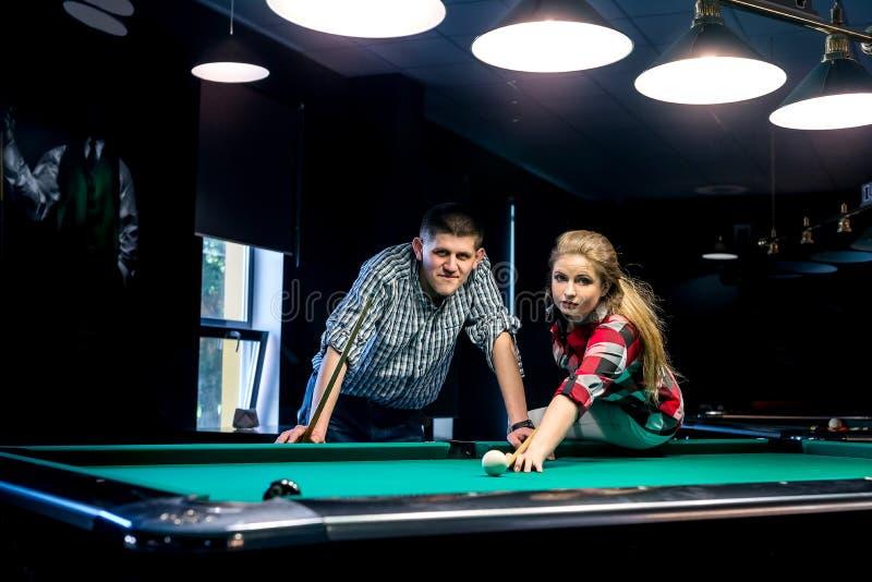 Belle coppie sorridenti in pub che gioca biliardo fotografia stock