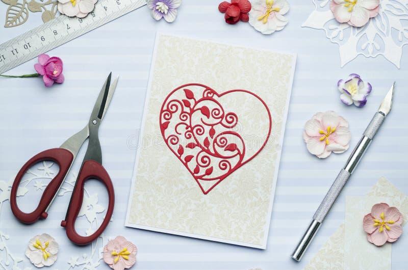 Belle coupe de coeur de papier sur la carte de voeux avec les fleurs de papier photos stock
