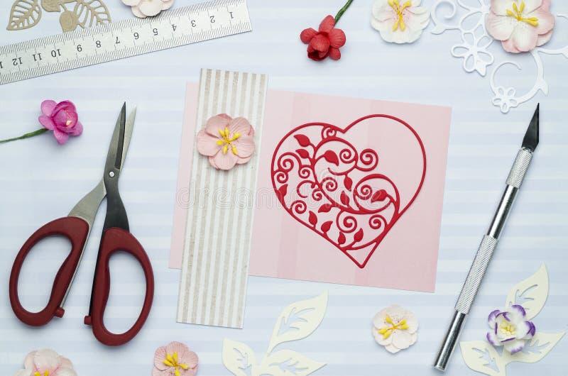 Belle coupe de coeur de papier sur la carte de voeux avec les fleurs de papier photo libre de droits