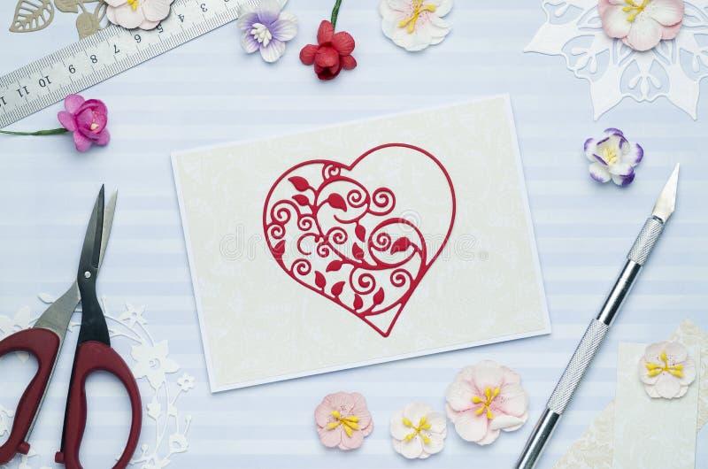 Belle coupe rouge de coeur de papier sur une carte de voeux avec les fleurs de papier photographie stock